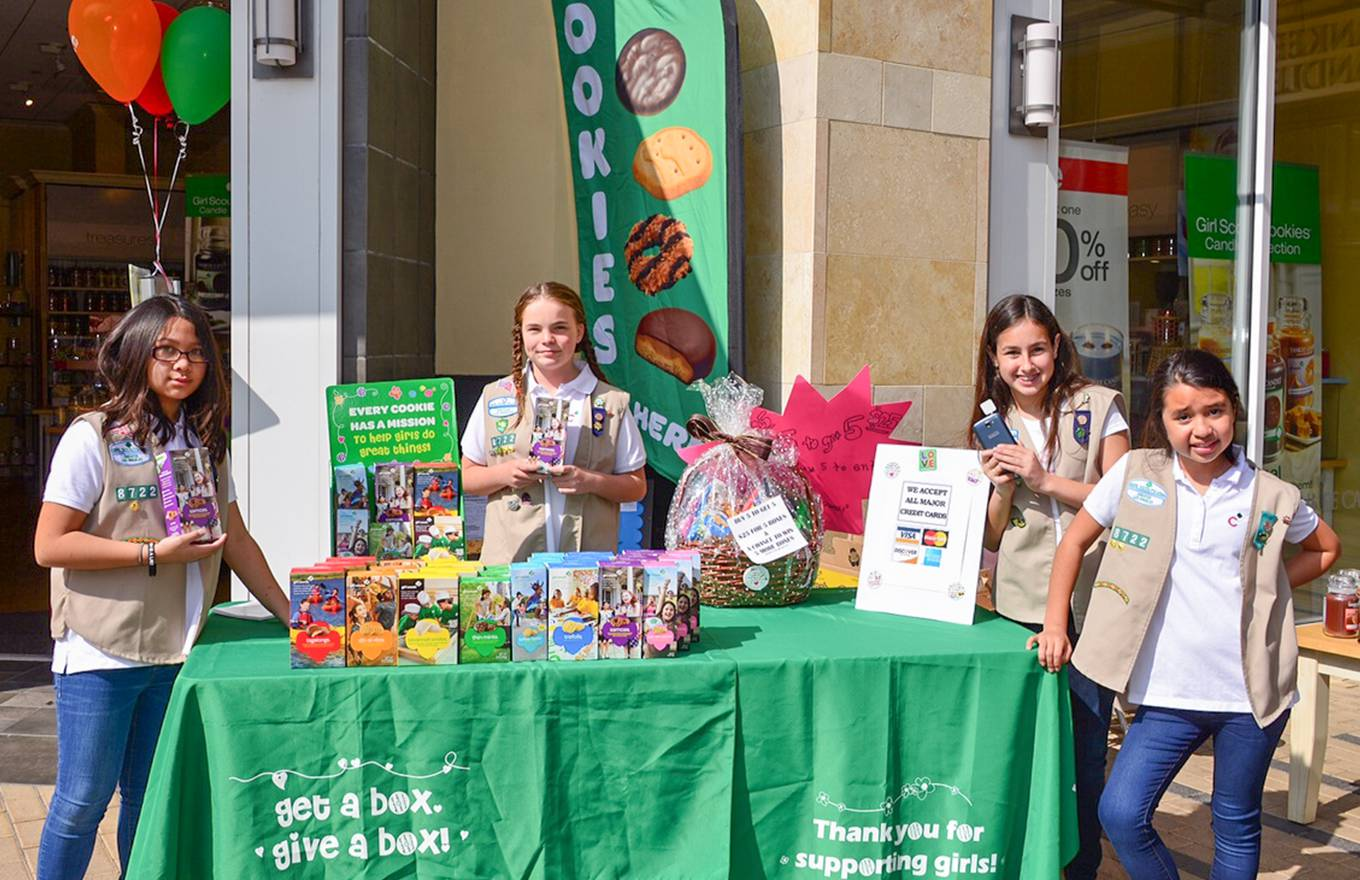 2 girl scouts selling cookies